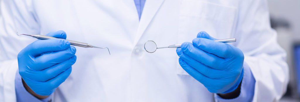 Dentist-Holding-Dental-Tools